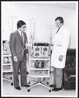 Unidentified man and Herschel Harter examining a dialysis machine.