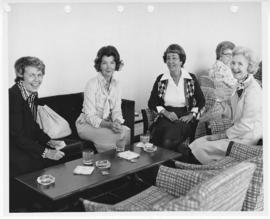 Four seated women with cocktails.