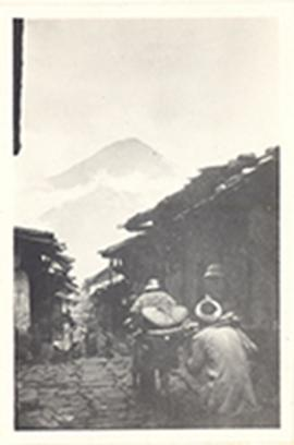 Stone-paved village street with men carrying loads and a mountain in the background, China.