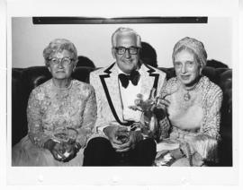 Man and two women wearing formal attire, sitting together on a sofa holding wineglasses.