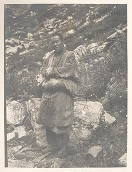Portrait of a man standing outside by a rocky hillside, China.