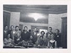Group portrait of Alice Cowdry seated at a banquet table with thirteen unidentified men and women.