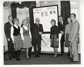 Group portrait of men and women gathered around a chart, Greater St. Louis Golf Classic.