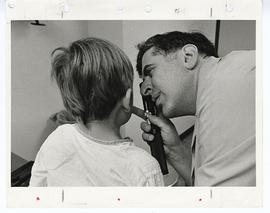 Arthur L. Prensky examining a pediatric patient with an opthalmoscope, St. Louis Children's Hospi...