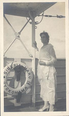 Portrait of an unidentified woman standing on the deck of the Siberia Maru next to a hanging life...