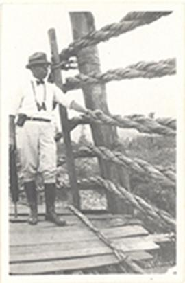 Paul H. Stevenson posing with binoculars and a folded parasol on a wood and rope bridge, China.