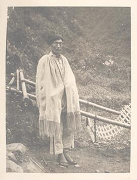 Portrait of a man standing next to a litter and wearing a long tasseled shawl, China.