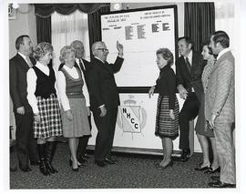 Group of men and women gathered around a chart, Greater St. Louis Golf Classic.