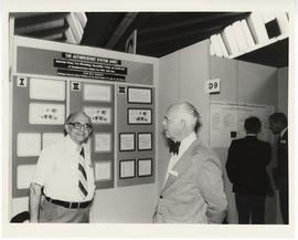 Alexander C. Sonnenwirth standing in front of his research display on the automicrobic system at ...
