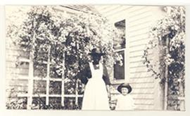 Portrait of E.V. Cowdry, Jr. and an African-American woman holding hands outside by a rose trellis.