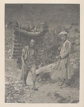 Two men on a dirt road, one of whom has a large bundle strapped to his back, Tibetan borderlands.