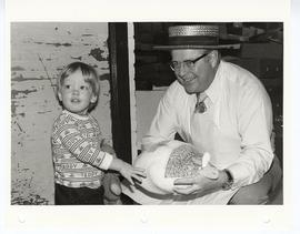 Man (possibley Linn B. Perkins) holding a frozen turkey next to a small child who is holding a te...