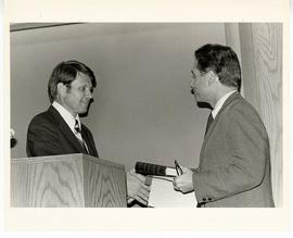 Donald R. Calvert standing behind a podium and handing a book to Samuel B. Guze at the Max A. Gol...