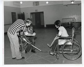 Adolescent boys playing wheelchair hockey.
