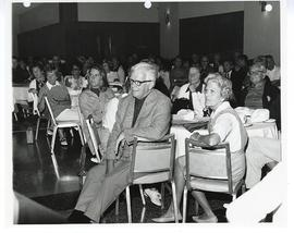 View of an audience seated at round tables.