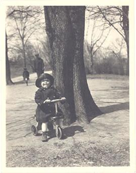 Young E.V. Cowdry, Jr. riding a tricycle.