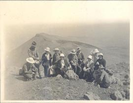 Group portrait of young Western hikers on a barren hilltop, China.