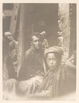 Men and a young boy in a crowded courtyard, China.