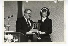 Linn B. Perkins handing an award plaque to Sister Mary Roch Rocklage, R.S.M.