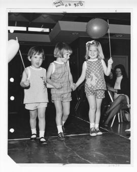 Three young girls with balloons holding hands on the runway at a St. Louis Children's Hospital Au...