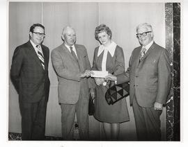 Unidentified man and woman presenting a check to Linn B. Perkins and C. Alvin Tolin.