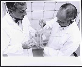 Dr. P. Roy Vagelos and Harry Huth displaying a glassblown lyophilizer.