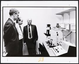 William H. Danforth, Gerald D. Fischbach, and an unidentified man looking at lab equipment.