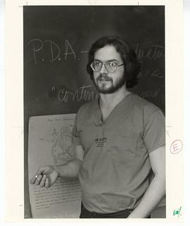 Man in scrubs standing in front of a blackboard, St. Louis Children's Hospital.