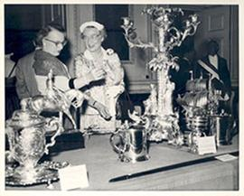 Unidentified woman and Alice Cowdry looking at a display of silver artifacts.