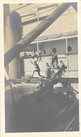 Group of children playing in and around the swimming pool on the deck of the Siberia Maru.