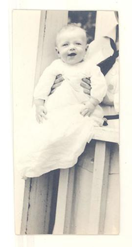 Portrait of an infant, likely Edmund Vincent Cowdry, Jr., being held on a porch railing.