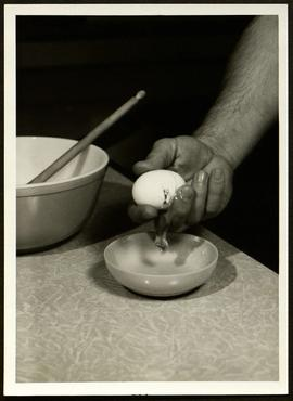 View of a man's hand cracking an egg into a bowl, Washington University School of Medicine, Progr...