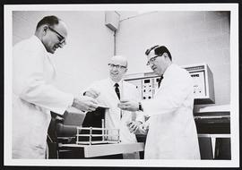 William Daughaday and two unidentified researchers in a laboratory.