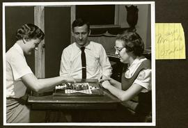 Three Washington University Occupational Therapy students playing a board game.