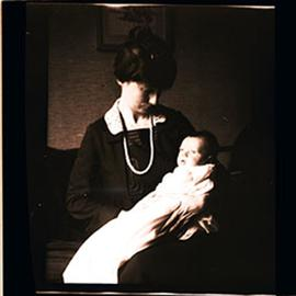 Alice Cowdry holding an infant, possibly Alice Moira Cowdry, in her lap.