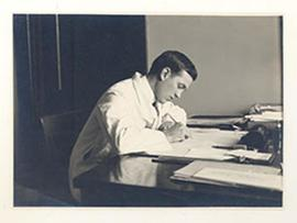 Portrait of E.V. Cowdry writing at a desk.
