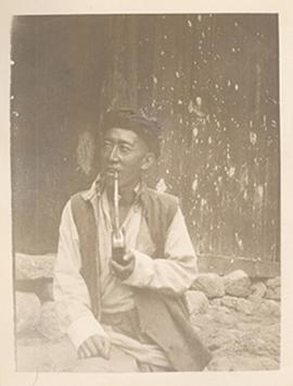 Seated man smoking a long wooden pipe, Tibetan borderlands.