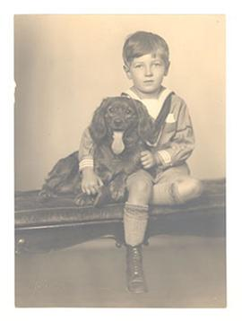 Studio portrait of E.V. Cowdry, Jr. with a dog.