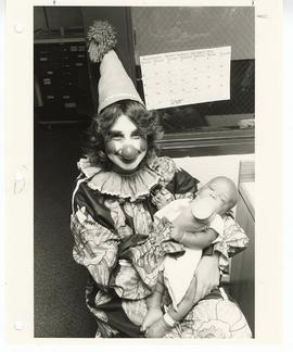 Woman dressed as a clown bottle feeding a baby, St. Louis Children's Hospital.
