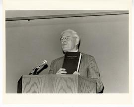 Hallowell Davis holding up a book and giving an address from a podium at the Max A. Goldstein rar...