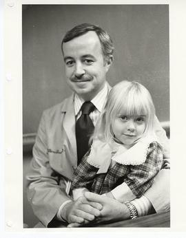 Dr. William T. Shearer, pediatrician, holding a young girl on his lap.