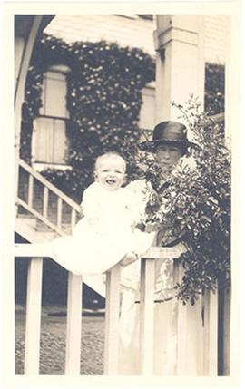 Alice Cowdry holding an infant, possibly Alice Moira Cowdry, on a porch railing.