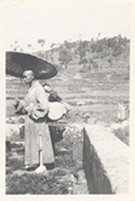 Robed man walking holding an parasol with a bundle strapped to his back, China.
