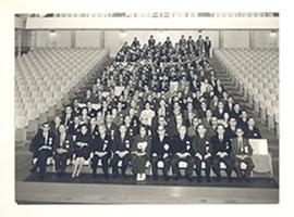 Group portrait of men and women seated in an auditorium for Takizawa's retirement, Chiba, Japan.