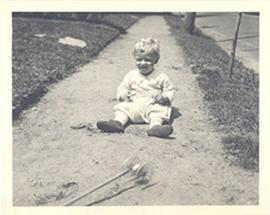 Edmund Vincent Cowdry, Jr. as a toddler, sitting outside on a gravel path.