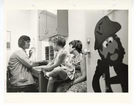 Staff member speaking to a mother with an infant in her lap in an office, St. Louis Children's Ho...