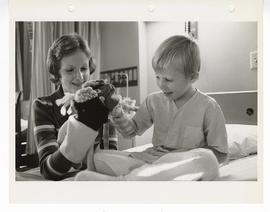 Woman playing hand puppets with a patient, St. Louis Children's Hospital.