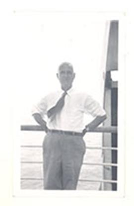 Portrait of E.V. Cowdry leaning against the rail of a ship.