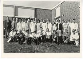 Group portrait with Alexander C. Sonnenwirth and colleagues in white coats posed outside.