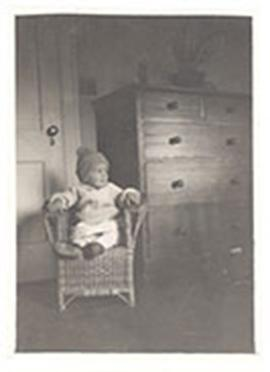 Edmund Vincent Cowdry, Jr. as an infant, sitting in a wicker chair next to a dresser.